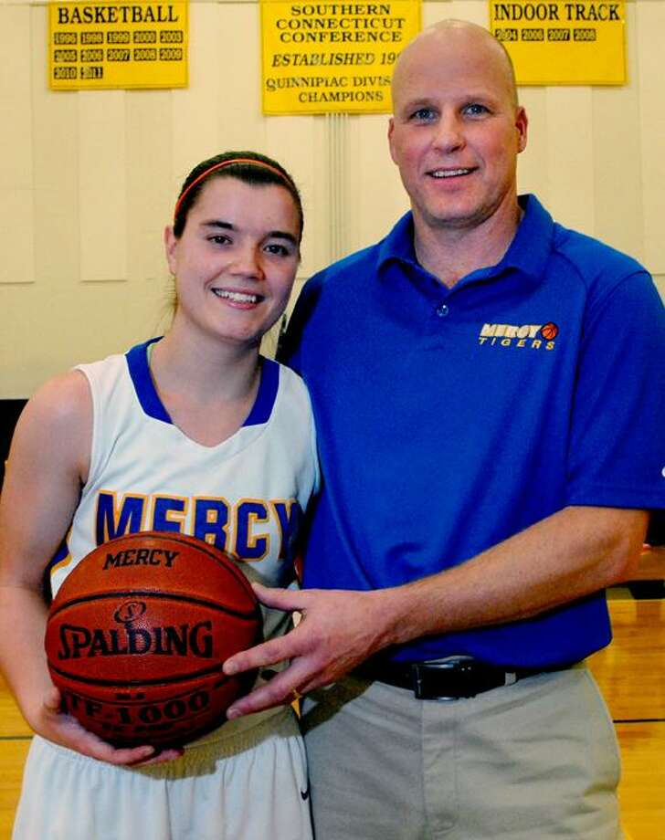 Catherine Avalone/The Middletown PressMercy senior captain Maria Weselyj with coach Tim Kohs scored 1,000 career points Friday night as the Tigers defeated the Westies 73-32 in Middletown.