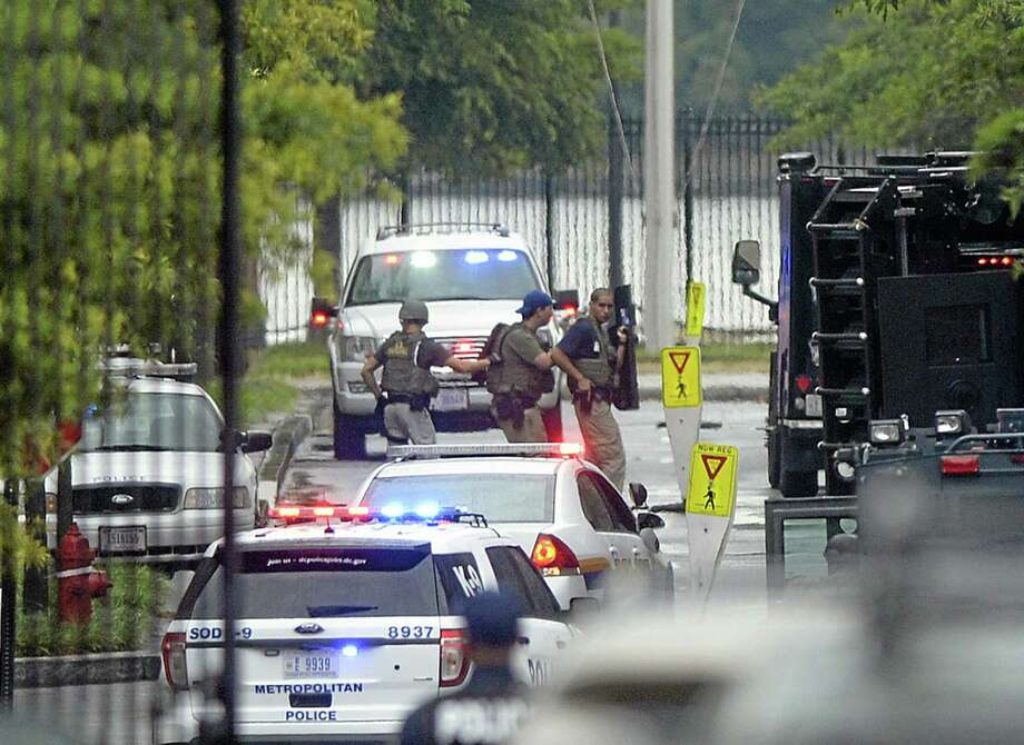 Law enforcement personnel are seen through the gate into the Washington Navy Yard in Washington, Monday, Sept. 16, 2013. At least one gunman opened fire inside a building at the Washington Navy Yard on Monday morning, and officials said several people were killed and more were wounded, including a law enforcement officer. (AP Photo/Susan Walsh) Photo: AP / AP