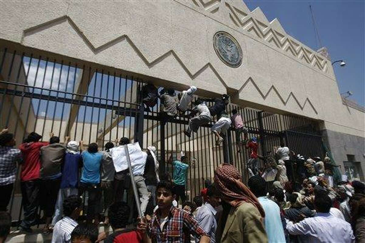 Yemeni protesters climb the gate of the U.S. Embassy during a protest Thursday about a film ridiculing Islam's Prophet Muhammad, in Sanaa, Yemen. Dozens of protesters gather in front of the US Embassy in Sanaa to protest against the American film