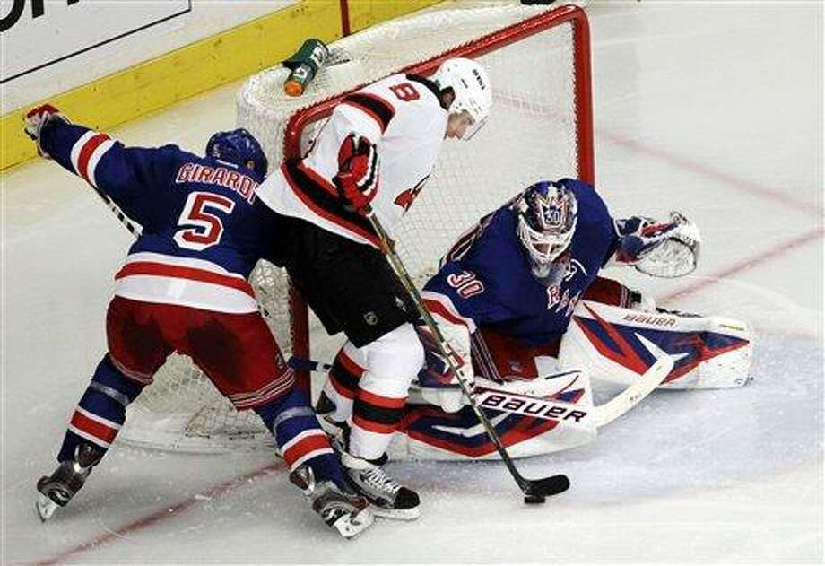 New York Rangers goalie Henrik Lundqvist, right, of Sweden, makes a save as New Jersey Devils' Dainius Zubrus (8), of Lithuania, attacks and Rangers' Dan Girardi (5) defends during the second period of Game 1 of their NHL hockey Stanley Cup Eastern Conference final playoff series, Monday, May 14, 2012, at New York's Madison Square Garden. (AP Photo/Julio Cortez) Photo: AP / AP