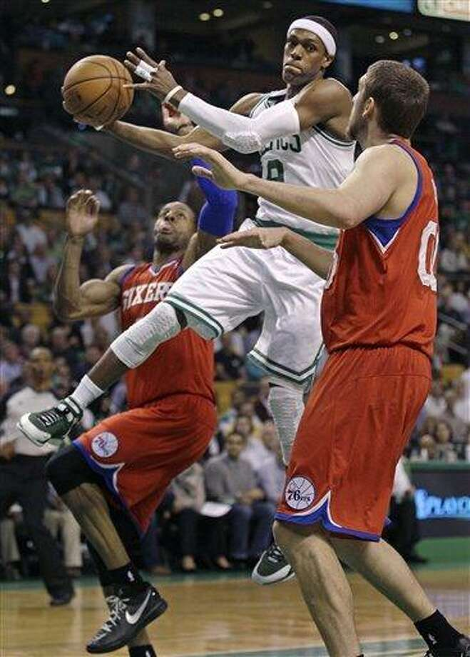Boston Celtics point guard Rajon Rondo (9) dumps off the ball as he is pressured by Philadelphia 76ers small forward Andre Iguodala, left, and center Spencer Hawes during the first quarter of Game 2 in their NBA basketball Eastern Conference semifinal playoff series in Boston, Monday, May 14, 2012. (AP Photo/Charles Krupa) Photo: AP / AP