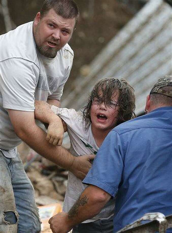 A child calls to his father after being pulled from the rubble of the Tower Plaza Elementary School following a tornado in Moore, Okla., Monday, May 20, 2013. A tornado as much as a mile (1.6 kilometers) wide with winds up to 200 mph (320 kph) roared through the Oklahoma City suburbs Monday, flattening entire neighborhoods, setting buildings on fire and landing a direct blow on an elementary school. (AP Photo Sue Ogrocki) Photo: AP / AP
