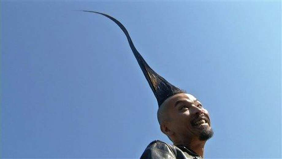 In this image taken from video, Kazuhiro Watanabe, 40, a fashion designer from Tokyo, shows off his 3-foot-8-point-6-inch hairdo in New York City's Washington Square Park on Wednesday. Associated Press Photo: AP / AP