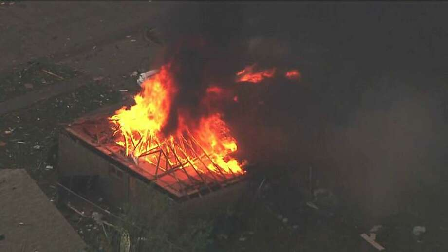 This photo provided by KFOR-TV shows a house fire outside Moore, Okla., Monday, May 20, 2013. A monstrous tornado as much as a mile wide roared through the Oklahoma City suburbs Monday, flattening entire neighborhoods, setting buildings on fire and landing a direct blow on an elementary school. (AP Photo/KFOR-TV) Photo: AP / AP