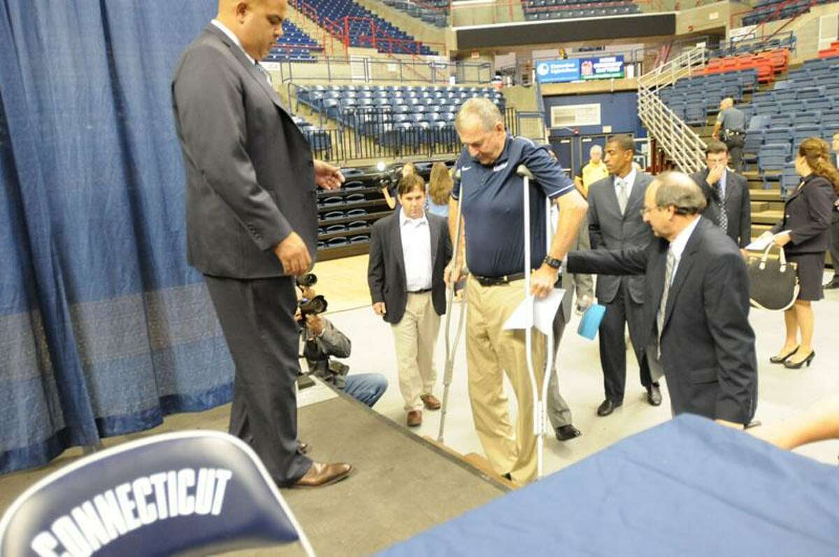 UConn men's basketball coach Jim Calhoun walks with the aid of crutches Thursday to a press conference to officially announce his retirement. Peter Hvizdak/Register
