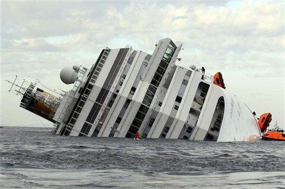 The luxury cruise ship Costa Concordia lies on its side after it ran aground off the tiny Tuscan island of Giglio, Italy, Sunday. Associated Press