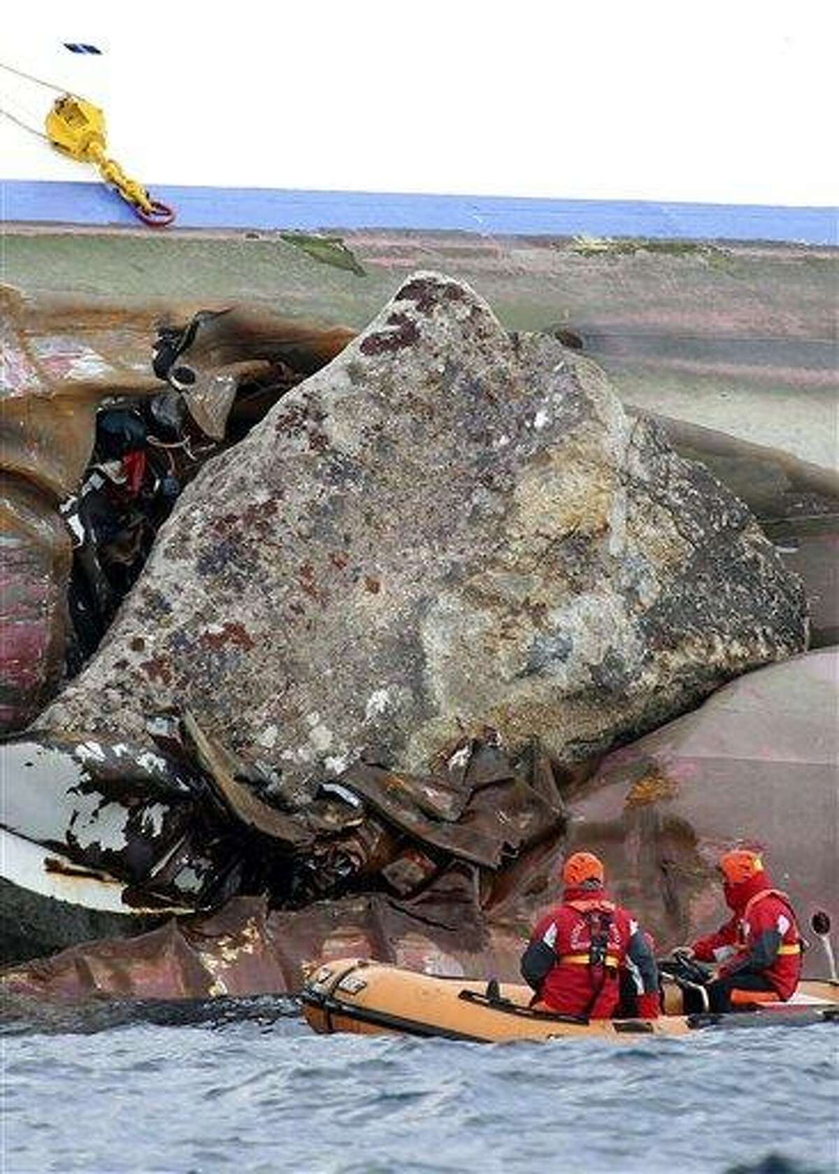 Firefighters on a dinghy look at a rock emerging from the side of the luxury cruise ship Costa Concordia, the day after it ran aground off the Tuscan island of Giglio, Italy, Sunday. Associated Press