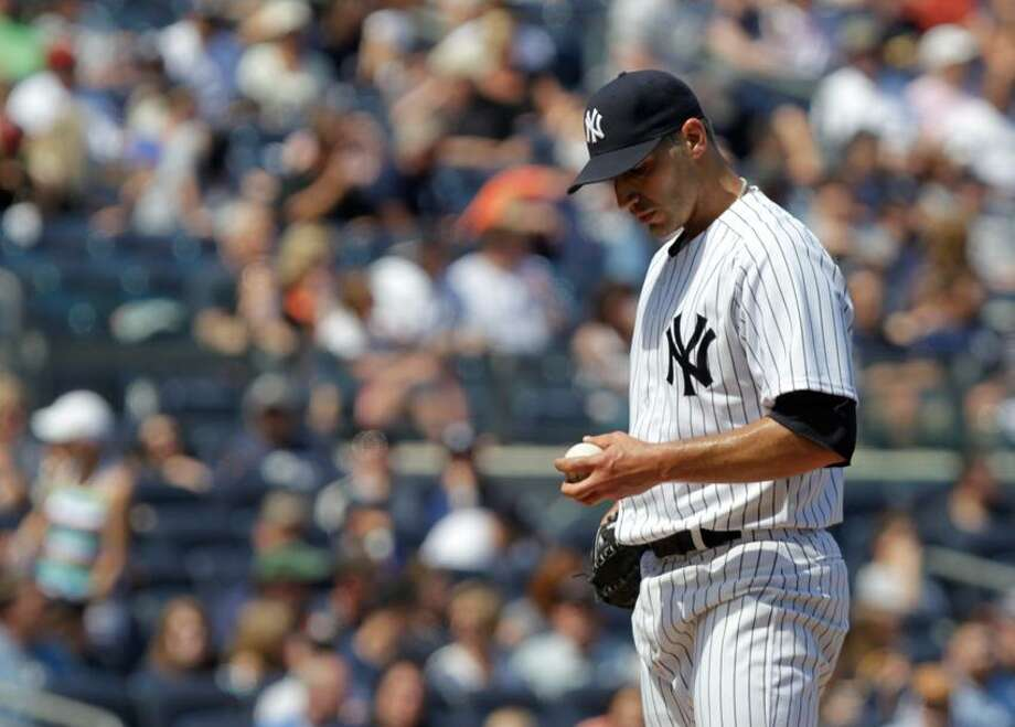 New York Yankees starting pitcher Andy Pettitte looks at the ball after Seattle Mariners' Casper Wells hit a home run during the sixth inning of a baseball game at Yankee Stadium in New York, Sunday, May 13, 2012.  (AP Photo/Seth Wenig) Photo: AP / AP2012