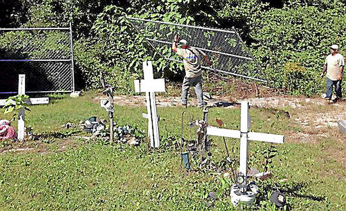 Workers erect a fence Wednesday, Sept. 18, 2013, around the perimeter of the site where The Station nightclub fire killed 100 people in 2003 in West Warwick, R.I. The fence, which from Wood & Wire Fence Co., Inc. donated, will close the site to visitors so a permanent memorial can be constructed. Since the fire, a makeshift memorial of homemade crosses and other mementos of those who died have marked the site. (AP Photo/Michelle R. Smith)