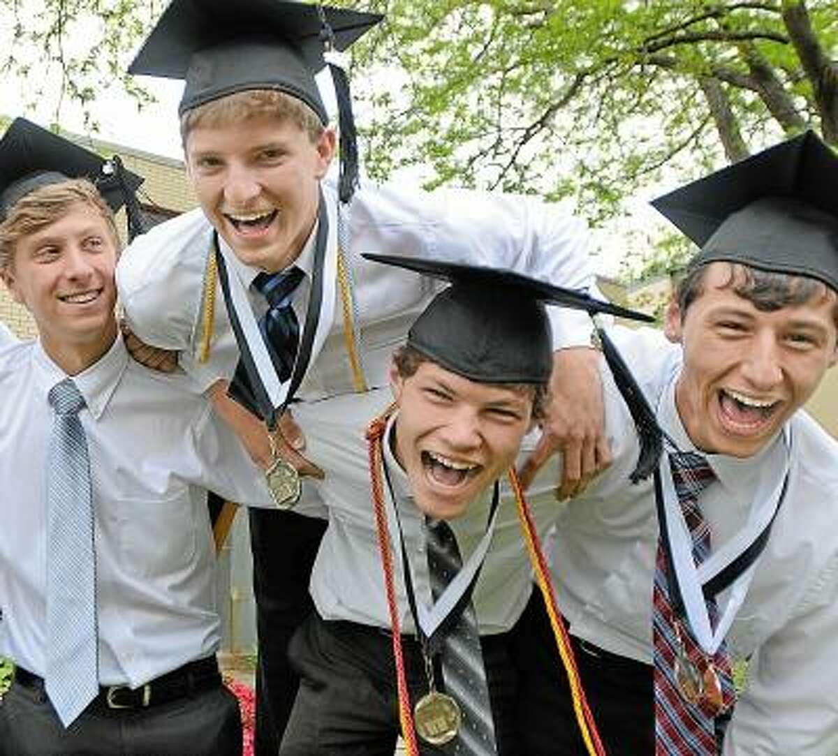 Members of Xavier's class of 2013, Adam Boyington, of Haddam, Middletown residents Corey Danko, Gavin Clemmey, school president, and Hamden resident Zac Camner celebrate after receiving their diplomas at the Forty-seventh Commencement Sunday morning. All are members of Xavier's Ultimate Frisbee team. Catherine Avalone/The Middletown Press