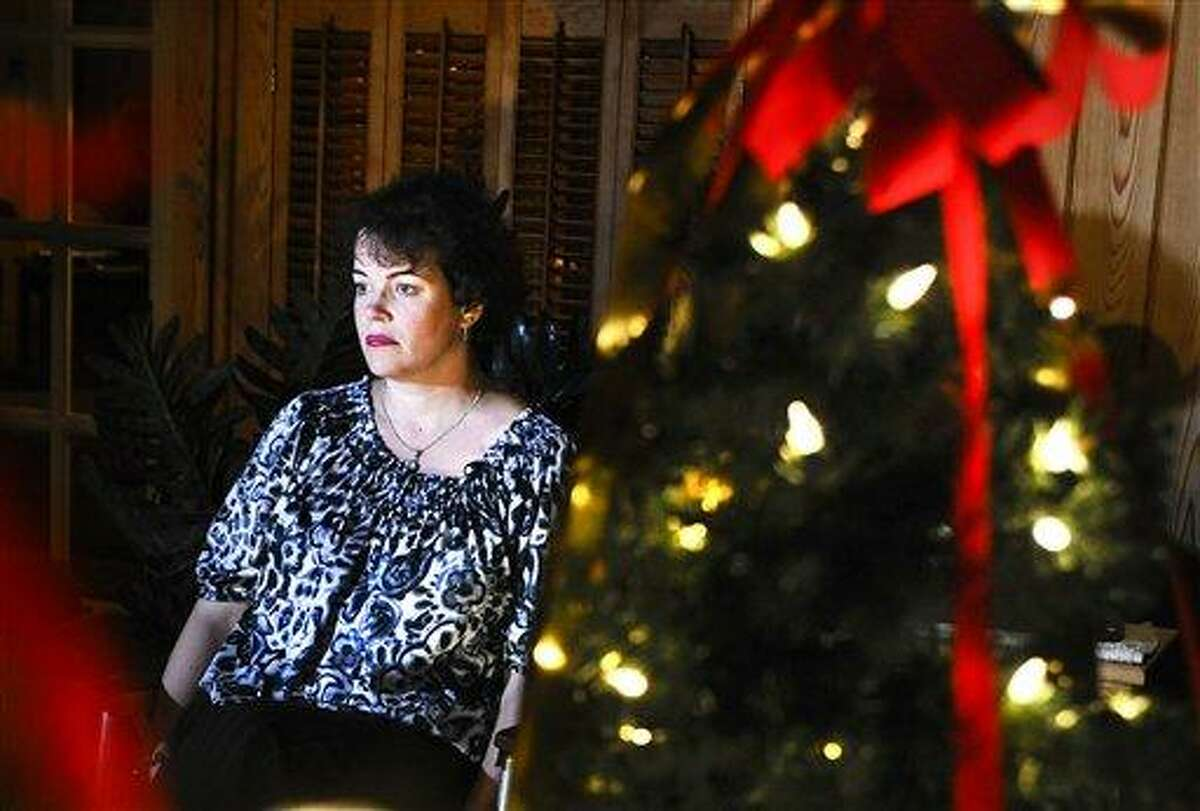 Veronique Pozner sits next to a decorated tree, picked out by her son Noah, at a friend's house during an interview with The Associated Press in Danbury. AP Photo/Jessica Hill