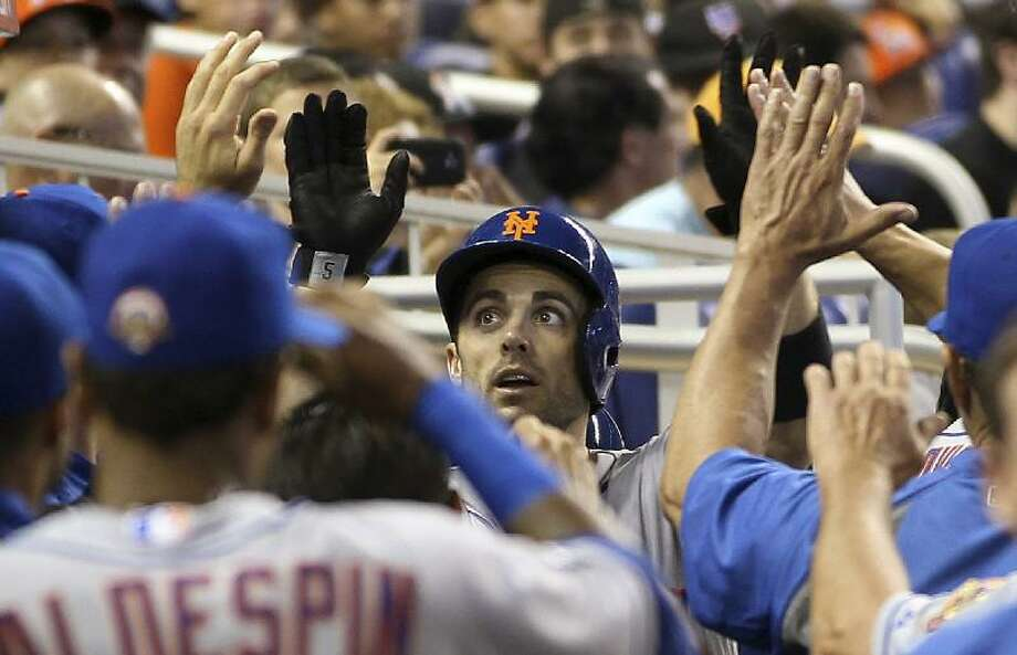 ASSOCIATED PRESS New York Mets' David Wright, center, celebrates with teammates in the dugout after hitting a third-inning home run against the Miami Marlins on Saturday in Miami. The Mets won the game 9-3.