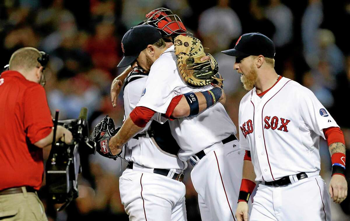 The Red Sox's John Lackey, center right, hugs Jarrod Saltalamacchia, center left, after pitching a complete game and defeating the Baltimore Orioles 3-1 as the Red Sox wrapped up a post-season berth.