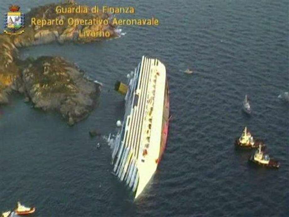 This aerial video image taken from a helicopter and released by the Italian Guardia di Finanza (Border Police) shows the luxury cruise ship Costa Concordia as it lies on its side after the ship ran aground off the tiny Tuscan island of Giglio, Italy, Saturday. Water was pouring in through a 160-foot (50-meter) gash in the hull and forcing the evacuation of some 4,200 people from the listing vessel. Associated Press Photo: ASSOCIATED PRESS / AP2012