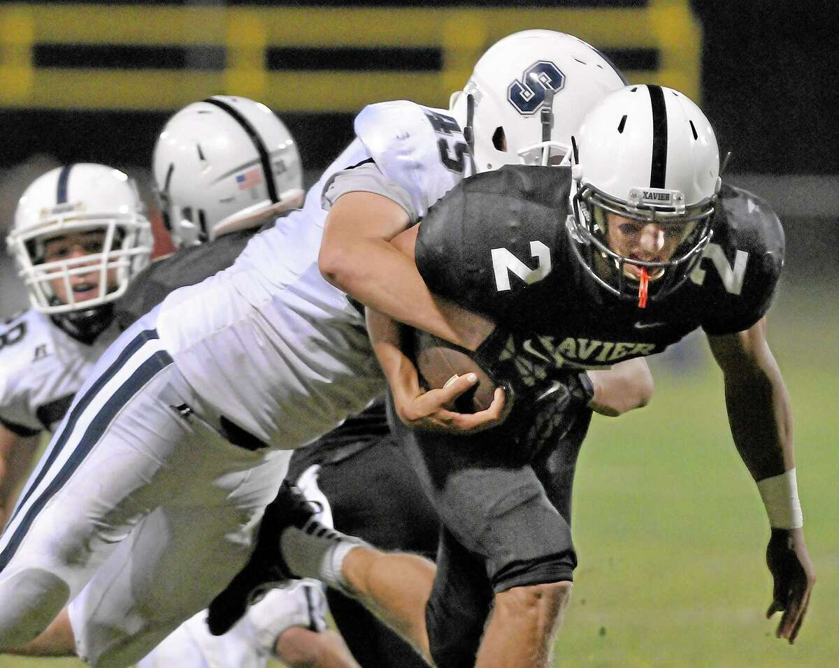 Xavier senior quarterback and captain Joe Carbone runs the ball against Staples Wednesday evening at Palmer Field. Catherine Avalone - The Middletown Press