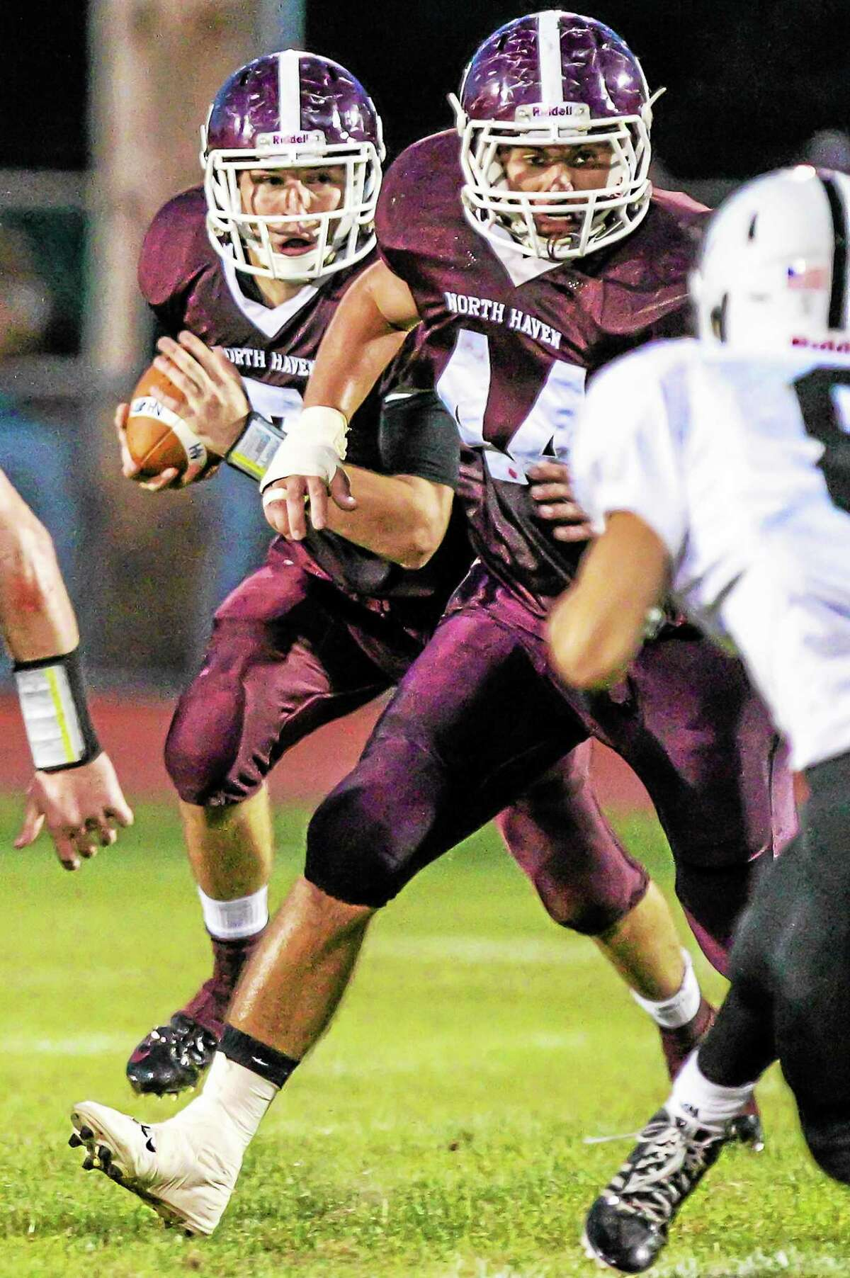 North Haven quarterback Mike Halloran gets blocking from Patrick Mikos(44) en route to a big gain in Friday's 42-28 victory over No. 2 Xavier