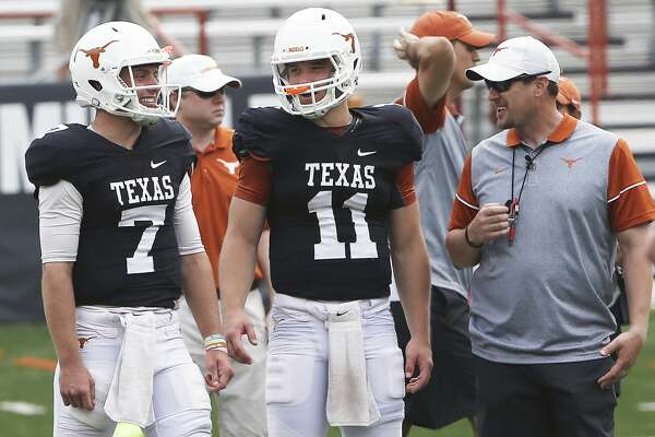 Quarterbacks Shane Buechele (7) and Sam Ehlinger share a laugh with coach Tom Herman as the Texas Longhorns play their Orange-White spring game on April 15, 2017.