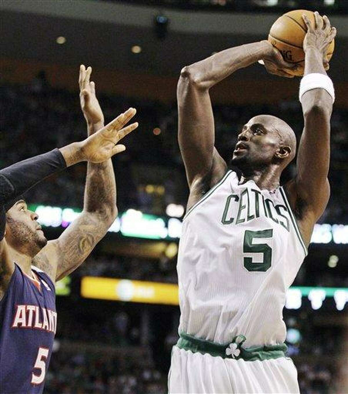 Boston Celtics power forward Kevin Garnett (5) shoots over Atlanta Hawks power forward Josh Smith (5) during the first half of Game 6 in a first-round NBA basketball playoff series in Boston, Thursday, May 10, 2012. The Celtics won 83-80 and won the series 4-2 to advance to the second round. (AP Photo/Charles Krupa)