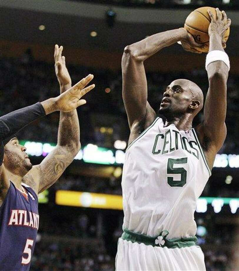 Boston Celtics power forward Kevin Garnett (5) shoots over Atlanta Hawks power forward Josh Smith (5) during the first half of Game 6 in a first-round NBA basketball playoff series in Boston, Thursday, May 10, 2012. The Celtics won 83-80 and won the series 4-2 to advance to the second round. (AP Photo/Charles Krupa) Photo: ASSOCIATED PRESS / AP2012