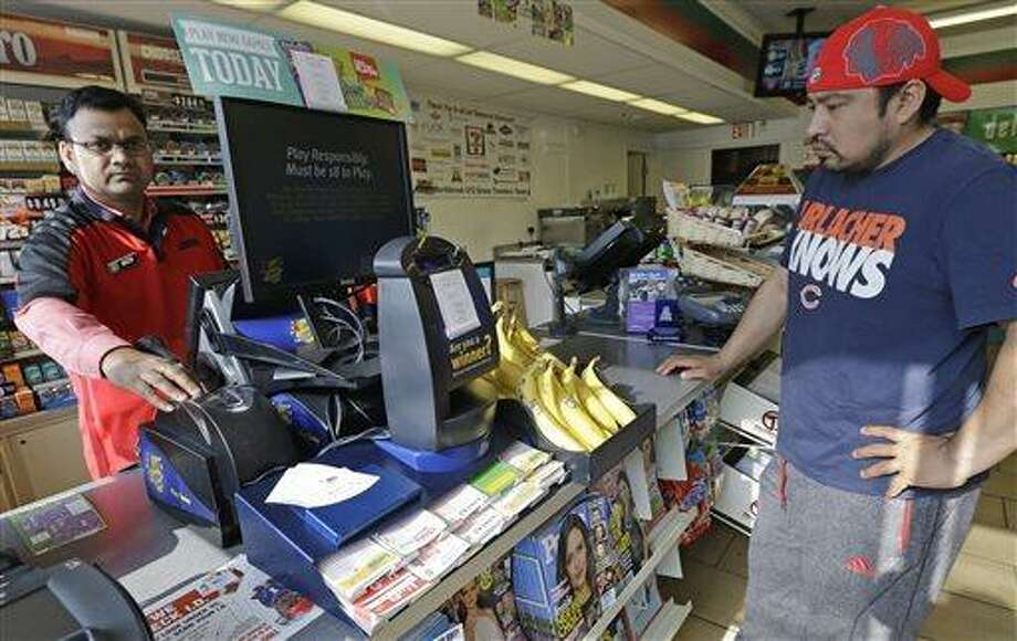 A customer, right, waits for his Powerball lottery ticket at a convenience store in Chicago on Saturday, May 18, 2013. A little more than a year after three tickets split a world-record lottery prize, the jackpot for Saturday's Powerball drawing was nearing historic territory. Should nobody pick the correct six numbers, the prize money will roll over to next week's drawing and almost certainly eclipse the $656 million doled out to winners in Illinois, Kansas and Maryland in the Mega Millions game in March 2012. (AP Photo/Nam Y. Huh) Photo: AP / AP