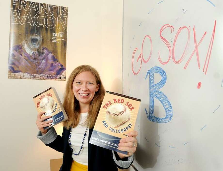 """Chelsea Harry, a philosophy professor at Southern Connecticut State University, 31, who has written a book titled """"The Red Sox and Philosophy - Green Monster Meditations"""", in her office at S.C.S.U. Friday, September 6, 2012. She believes that the Boston Red Sox are """"Zen"""" and mostly follow an Eastern philosophy with an emphasis on being a team, while the New York Yankees would be Western, e.g., out for the self. Photo by Peter Hvizdak / New Haven Register"""