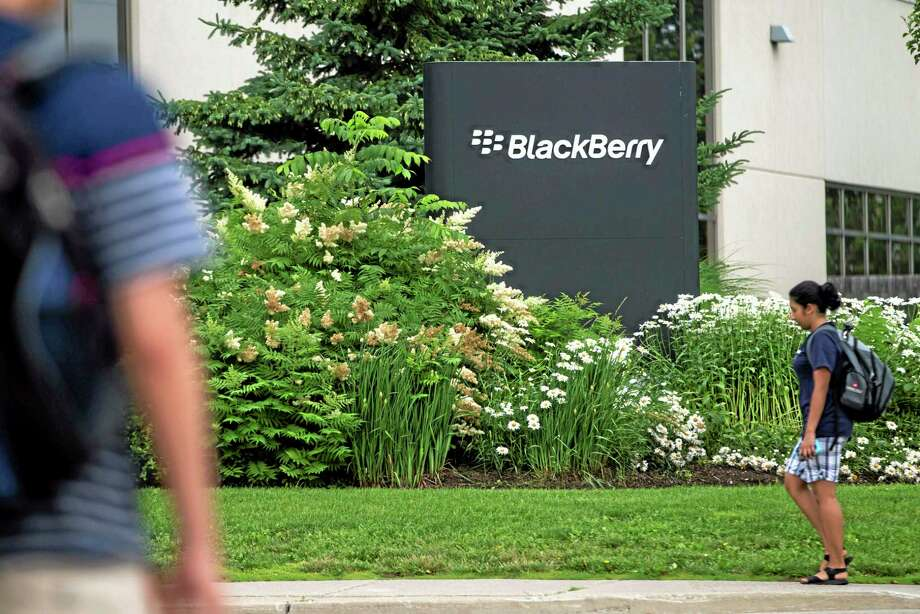 FILE- In this Tuesday, July 9, 2013, file photo, pedestrians walk near BlackBerry's headquarters in Waterloo, Ontario, on the morning of the company's Annual General Meeting. BlackBerry said Friday, Sept. 20, 2013,  it will lay off 4,500 employees, or 40 percent of its global workforce, and is announcing a nearly $1 billion second-quarter loss in a surprise early release of earnings.  (AP Photo/The Canadian Press,  Geoff Robins, File) Photo: AP / CP