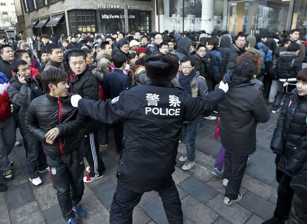 A policeman tries to drag away people who refused to leave the Apple Store in Beijing Friday. An angry crowd shouted and threw eggs at Apple's Beijing flagship store after it failed to open on schedule Friday to sell the popular new iPhone 4S model. (AP Photo/Andy Wong)