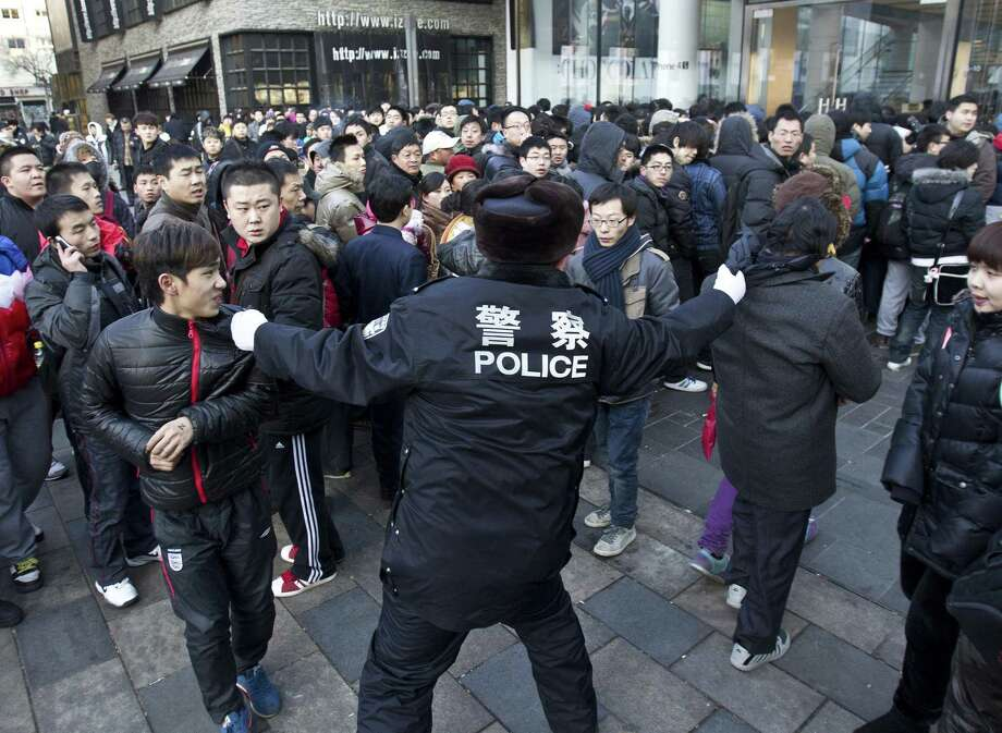 A policeman tries to drag away people who refused to leave the Apple Store in Beijing Friday. An angry crowd shouted and threw eggs at Apple's Beijing flagship store after it failed to open on schedule Friday to sell the popular new iPhone 4S model. (AP Photo/Andy Wong) Photo: ASSOCIATED PRESS / AP2012