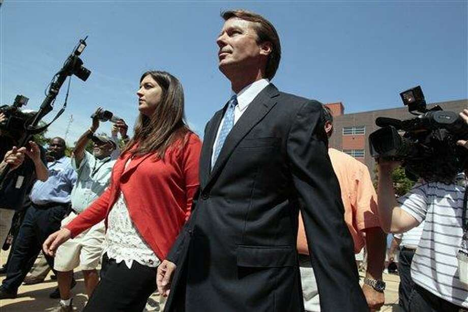 In this June 2011 file photo, former presidential candidate John Edwards leaves federal court with his daughter Cate, following an appearance in Winston-Salem, N.C., where a grand jury indicted Edwards, accusing him of trying to protect his political ambitions by soliciting and secretly spending more than $925,000 to hide his mistress and their baby from the public.  Associated Press Photo: AP / 2011 AP