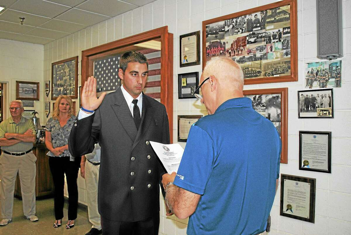 Firefighter Geoffrey DeFrancesco, of Middletown, is sworn in at Middletown's South District Firehouse Friday afternoon. (Viktoria Sundqvist - The Middletown Press)