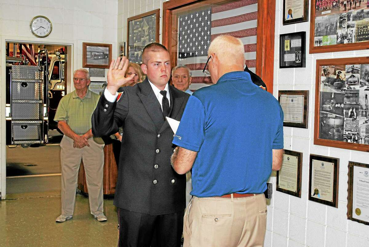 Firefighter Nicholas Fischer, of Colchester, is sworn in at Middletown's South District Firehouse Friday afternoon. (Viktoria Sundqvist - The Middletown Press)