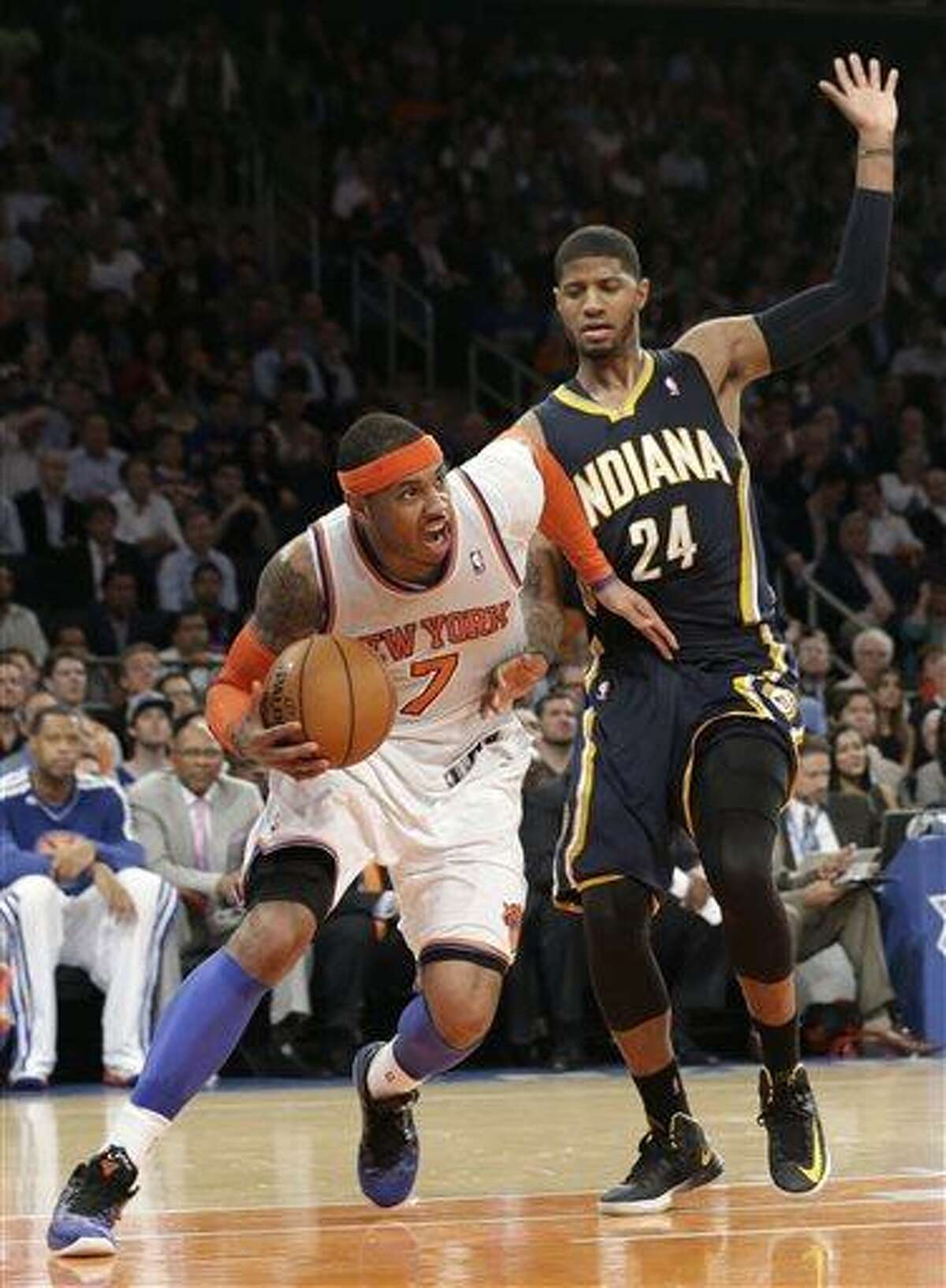 New York Knicks' Carmelo Anthony, left, drives against Indiana Pacers' Paul George in the second half of Game 5 of an Eastern Conference semifinal in the NBA basketball playoffs, at Madison Square Garden in New York, Thursday, May 16, 2013. The Knicks won 85-75. (AP Photo/Julio Cortez)