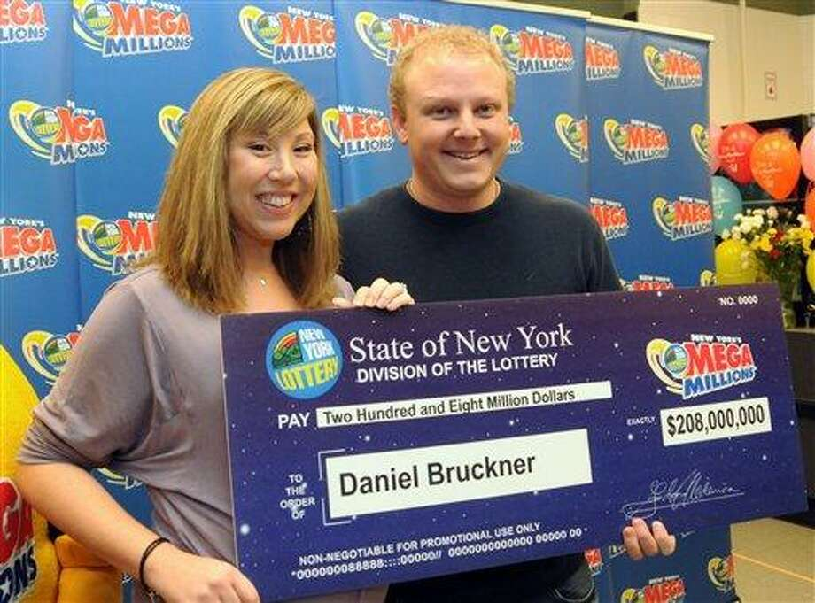 Daniel Bruckner, 35, alongside his wife, Christine, claims his $208 million Mega Millions jackpot, Friday, Jan. 13, 2012, at King Kullen supermarket where the winning ticket was sold, in Middle Island, N.Y. Bruckner, of San Jose, Calif., is a Silicon Valley financial analyst. (AP Photo/Newsday, James Carbone)  NYC LOCALS OUT Photo: AP / Newsday