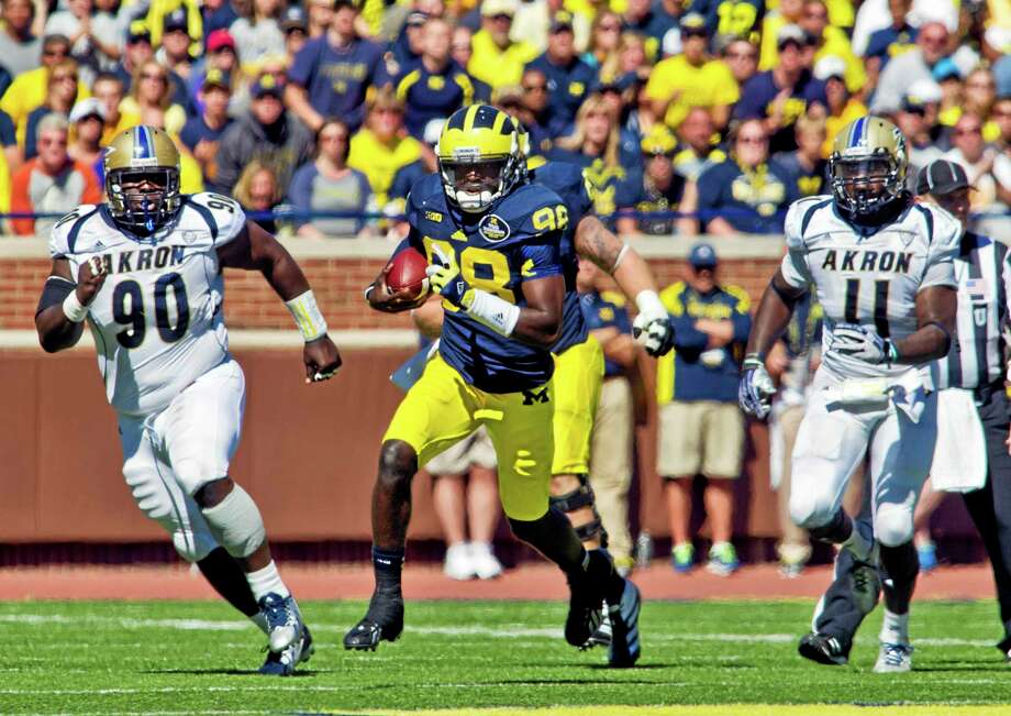 UConn will need to contain Michigan quarterback Devin Gardner (98) in tonight's game at Rentschler Field, which will be shown on ABC. Photo: Tony Ding  — The Associated Press  / FR143848 AP