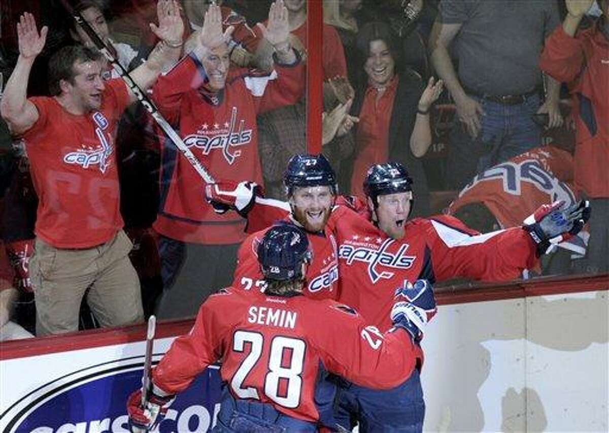 Washington Capitals left wing Jason Chimera, right, celebrates a goal against the New York Ranger with teammates defenseman Karl Alzner, center, and left wing Alexander Semin (28) in the second period of Game 6 of a second-round NHL hockey Stanley Cup playoff series in Washington, Wednesday, May 9, 2012. The Capitals defeated the Rangers 2-1. (AP Photo/Susan Walsh)
