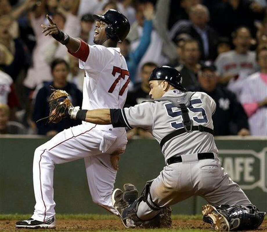 Boston Red Sox's Pedro Ciriaco (77) reacts after scoring the winning run on a single by Jacoby Ellsbury as New York Yankees catcher Russell Martin shows the ball to the umpire during the ninth inning of a baseball game at Fenway Park in Boston, Tuesday, Sept. 11, 2012. The Red Sox won 4-3. (AP Photo/Elise Amendola) Photo: AP / AP