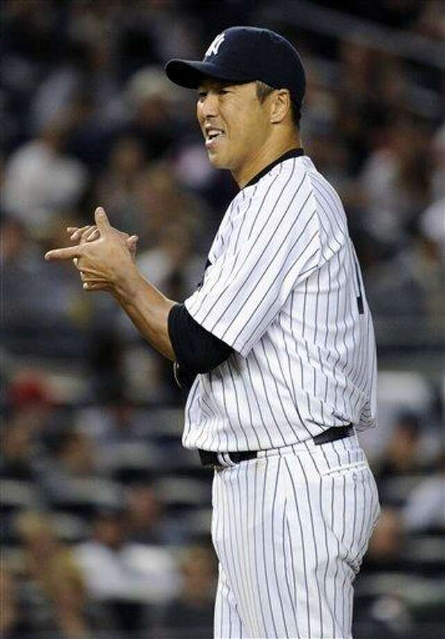 New York Yankees pitcher Hiroki Kuroda rubs up a new ball during the seventh inning of a baseball game against the Toronto Blue Jays Friday, May 17, 2013, at Yankee Stadium in New York. (AP Photo/Bill Kostroun) Photo: AP / FR51951 AP