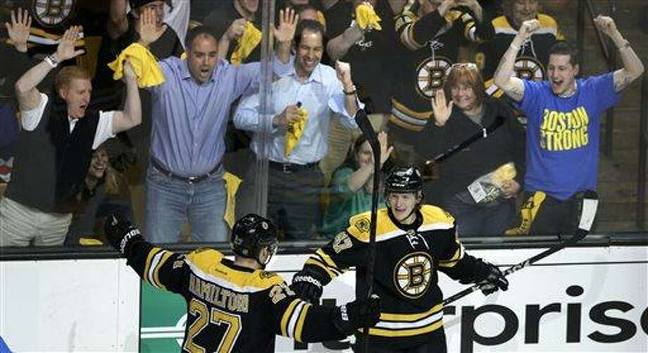 Fans, top, celebrate as Boston Bruins defenseman Torey Krug, front right, is congratulated by teammate Dougie Hamilton after his goal against the New York Rangers during the third period in Game 1 of an NHL hockey playoffs Eastern Conference semifinal game in Boston, Thursday, May 16, 2013. (AP Photo/Charles Krupa) Photo: AP / AP