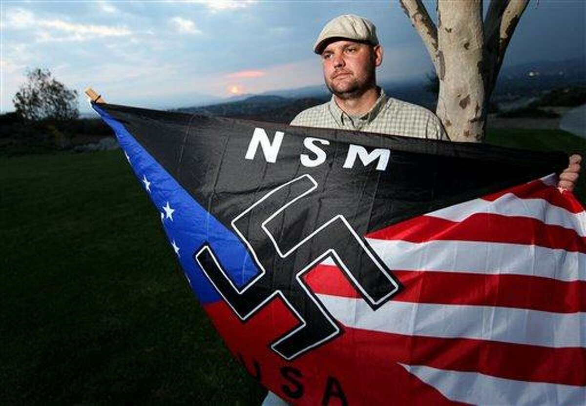 Jeff Hall, who was killed by his son, holds a Neo Nazi flag while standing at Sycamore Highlands Park near his home in Riverside, Calif. AP Photo/Sandy Huffaker