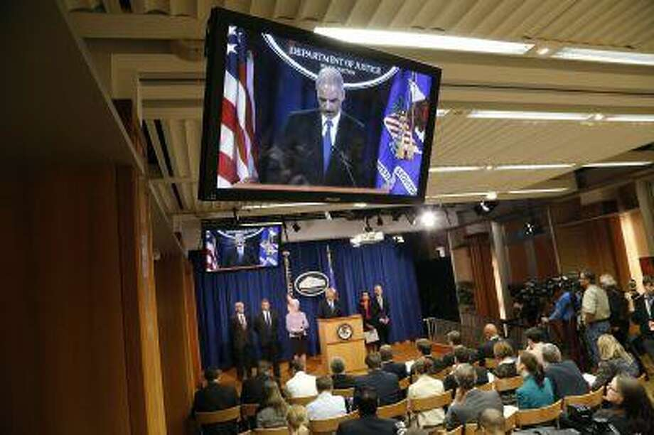 U.S. Attorney General Eric Holder appears on television monitors as he stands at the lectern to address a news conference to announce Medicare Fraud Strike Force law enforcement actions at the Justice Department in Washington May 14, 2013. Holder is likely to face a storm of questions over the Justice Department's controversial decision to seize telephone records of the Associated Press, a move denounced by critics as a gross intrusion into freedom of the press. REUTERS/Jonathan Ernst (UNITED STATES - Tags: POLITICS CRIME LAW MEDIA) Photo: REUTERS / X01676
