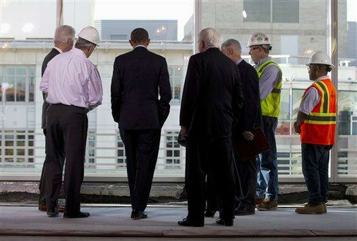 In this December 2011 file photo, President Barack Obama, second from left, accompanied by U.S. Chamber of Commerce President and CEO Thomas Donohue, third from left, tour a building under construction in Washington. A bullish, yet wary Obama is highlighting recent economic bright spots while taking care not to overstate a recovery that still has not lifted millions out of joblessness. Associated Press