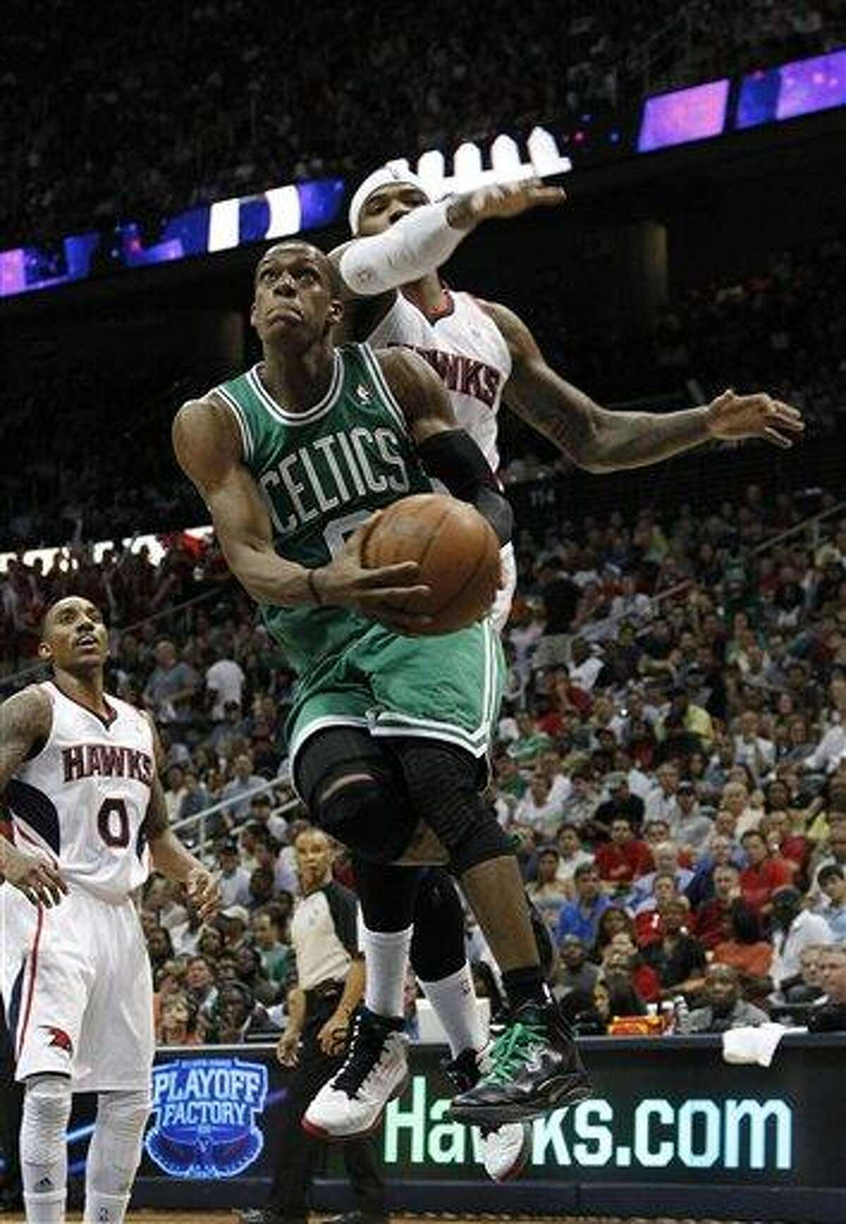 Boston Celtics point guard Rajon Rondo (9) drives as Atlanta Hawks power forward Josh Smith (5) defends during the second half of Game 5 of an NBA first-round playoff series basketball game Tuesday, May 8, 2012, in Atlanta. (AP Photo/John Bazemore)