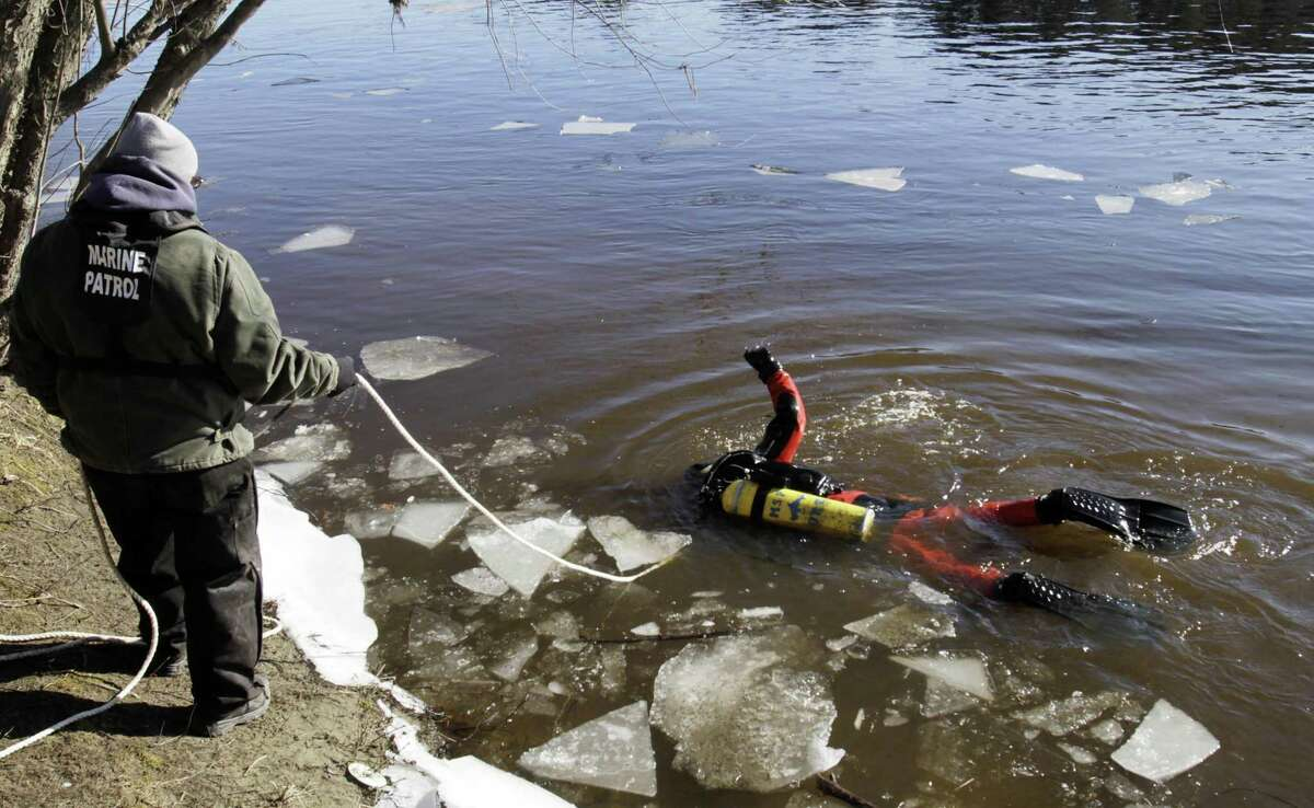 A diver maneuvers around sheets of ice as he signals to a Maine Warden while searching the Kennebec River in Waterville, Maine, Wednesday for 20-month-old Ayla Reynolds who was reported missing since December. Associated Press