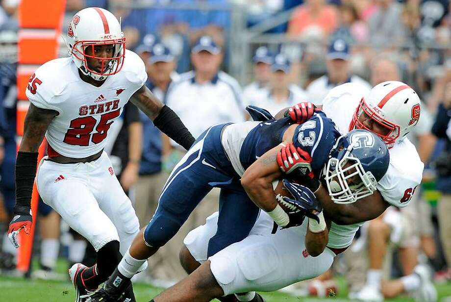 Connecticut's Lyle McCombs (43) is tackled by North Carolina State's Thomas Teal, right, as North Carolina State's Dontae Johnson looks on during the first half of their football game Saturday in East Hartford. Associated Press Photo: ASSOCIATED PRESS / AP2012