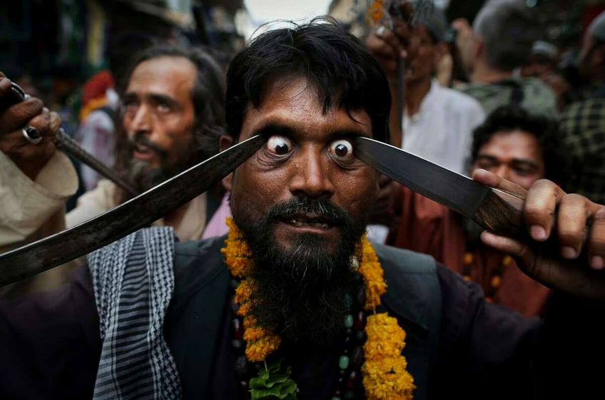 In this Saturday, May 11, 2013 photo, an Indian Muslim Sufi holy man self-flagellates himself with sharp objects during a procession at the shrine of Khwaja Moinuddin Chishti during the Urs festival in Ajmer, India. Thousands of Sufi devotees from different parts of India travel to the shrine for the annual festival, marking the death anniversary of Sufi Muslim saint Khwaja Moinuddin Chishti. (AP Photo/Kevin Frayer)