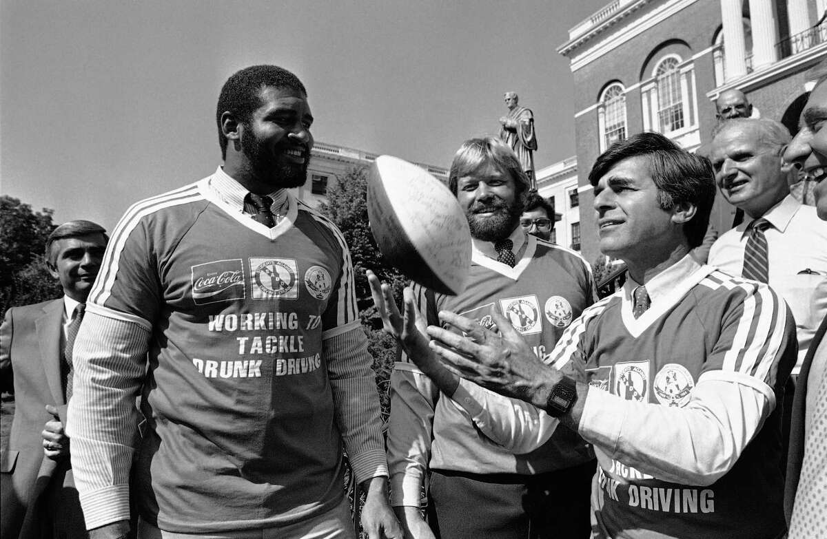 Massachusetts Governor Michael Dukakis tosses a football as New England Patriots players Brian Holloway, left, and Steve Nelson look on during a press conference on the Boston Statehouse steps on Sept. 24, 1984.