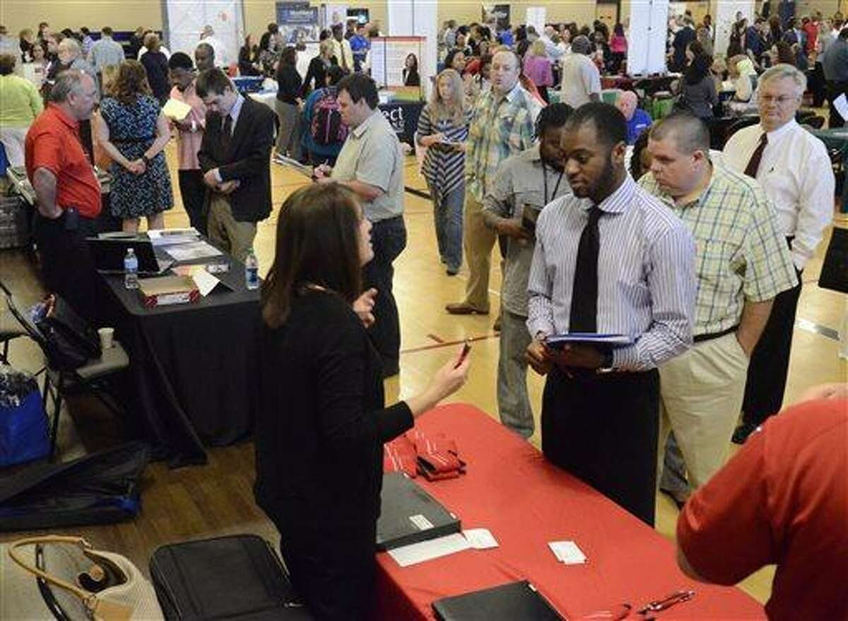 In this photo taken Thursday, May 9, 2013, Jennifer Wilhoit of U. S. Express, left, talks with Devin Washington while others wait in line as 63 companies participate in a job fair at the Brainerd Crossroads in Chattanooga, Tenn. The Labor Department reports on the number of Americans who applied for unemployment benefits last week on Thursday, May 16, 2013. (AP Photo/Chattanooga Times Free Press, John Rawlston)