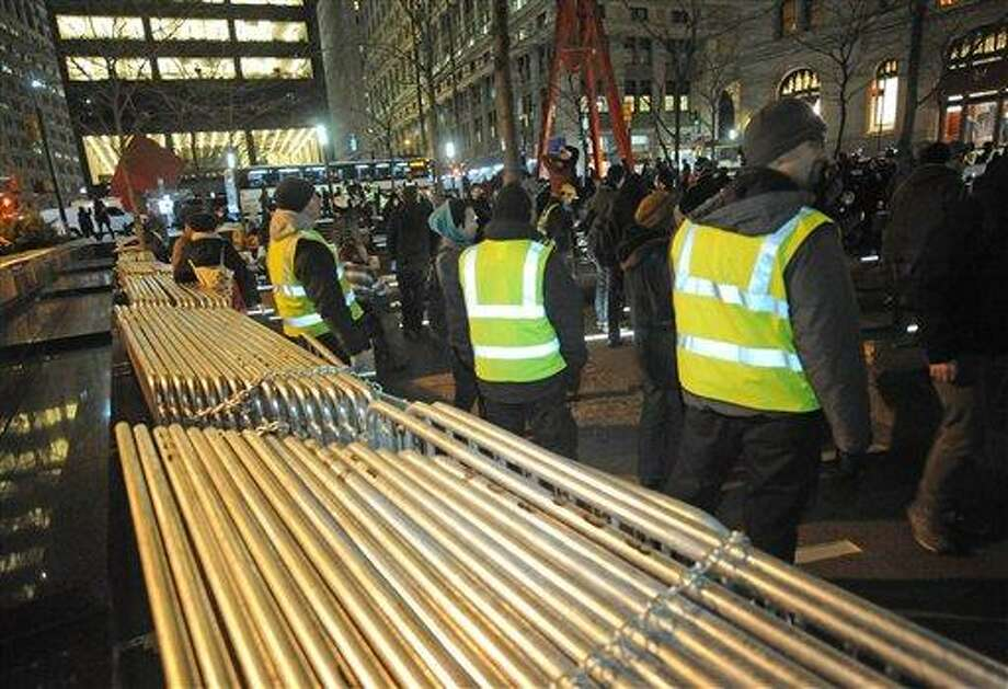 Security from Brookfield Properties, the owners of Zuccotti Park stand next to barricades that were removed from the park's perimeter as Occupy Wall Street protesters gather in the park Tuesday in New York. Barricades were removed by the owners Tuesday, allowing access into the park by the protesters. Associated Press Photo: AP / FR77522 AP