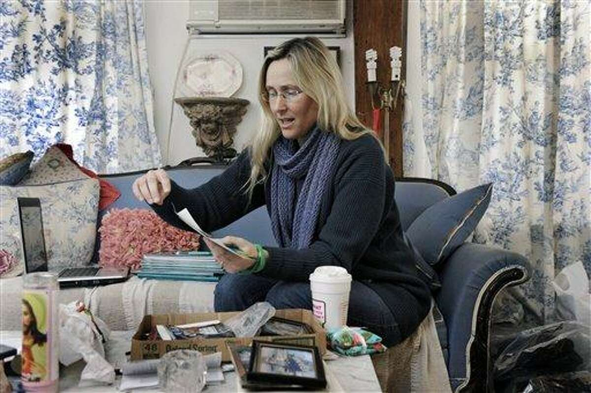 Scarlett Lewis, of Newtown looks through photographs of her son Jesse, who was killed in the Sandy Hook Elementary School shooting. AP Photo/The News-Times of Danbury, Carol Kaliff