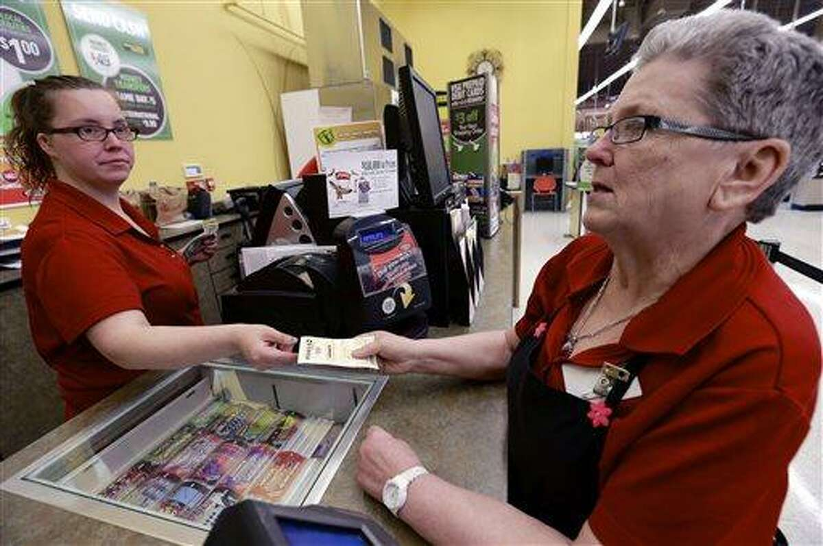 Sharon Brickey, right, purchases a Powerball ticket from Tiffany Enders, left, at a Baker's supermarket in Omaha, Neb., Wednesday, May 15, 2013. Enders had recently sold a million dollar Powerball ticket at the store. After weeks of rolling without a winner, the Powerball jackpot has once again ballooned in time for its Wednesday drawing, an estimated $360 million jackpot considered the third largest Powerball jackpot and the seventh largest jackpot in history. (AP Photo/Nati Harnik)